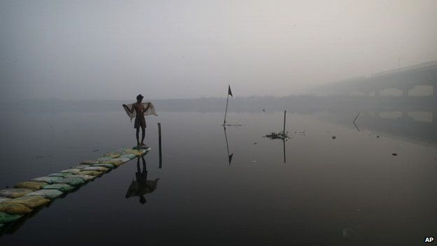 A man uses a cloth to dry himself after taking a dip in the polluted waters of the Yamuna River on a winter morning in New Delhi