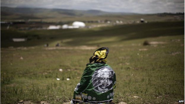 A woman looks on as South African former president Nelson Mandela's coffin is carried to his burial site during his state funeral in his home village in Qunu. Qunu's high school will receive 100,000 rand from his will.
