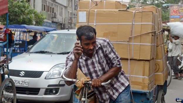 An Indian daily-wage labourer talks on his mobile phone as he transports goods on a rickshaw van down a busy street in New delhi on April 30, 2013
