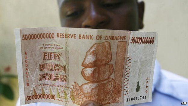 A Zimbabwean looks at a $50bn Zimbabwean issued on 13 January 2009