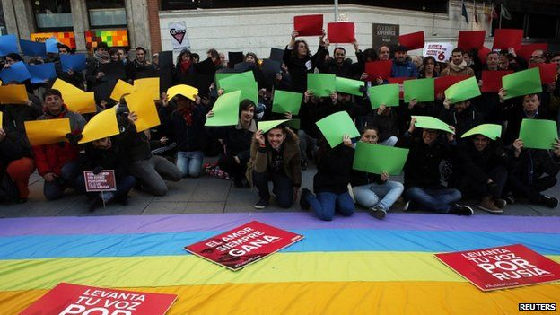 Demonstrators pose with the pieces of paper in the colours of the Olympic rings during a protest in Madrid against Russia's anti-gay laws ahead of the Sochi 2014 Olympic Games on 5 February 2014.