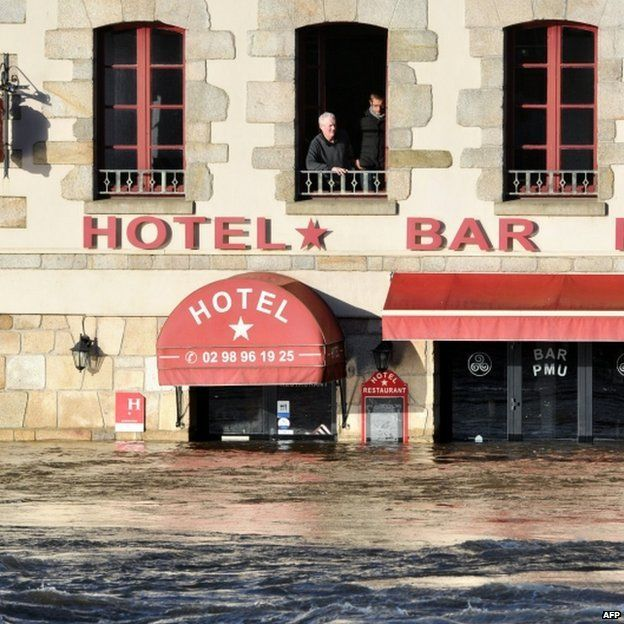 People look out of an upstairs window at flooding in Quimperle, France, 7 February