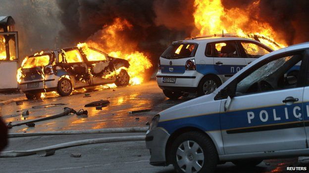 Cars burn as anti-government protesters clash with police in Sarajevo February 7, 2014.