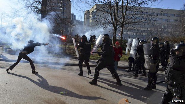 An anti-government protester throws a flare at riot police during clashes in Sarajevo February 7, 2014.
