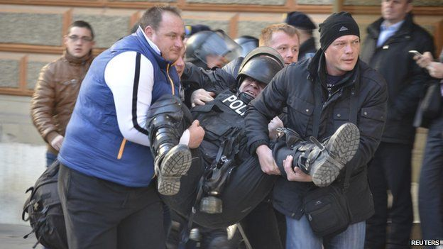 People help an injured policeman as anti-government protesters clash with police in Sarajevo February 7, 2014