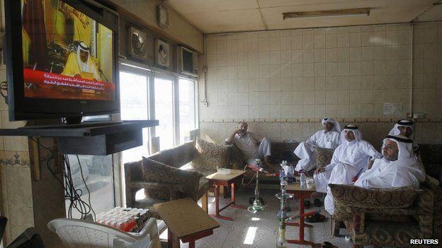 Qatari men watch a speech by Qatar's former emir in June 2013