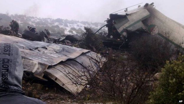 A man watches rescue workers working at the wreckage of Algerian military transport aircraft after it slammed into a mountain in the country's rugged eastern region