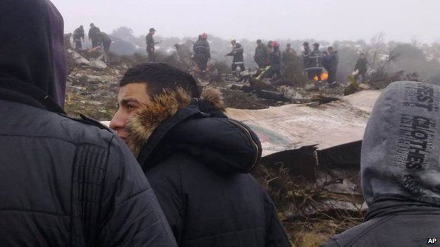 People watch rescue workers working at the wreckage of an Algerian military transport aircraft after it slammed into a mountain in the country's rugged eastern region