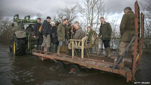Prince Charles sits on a tractor trailer as he visits the flood hit village of Muchelney