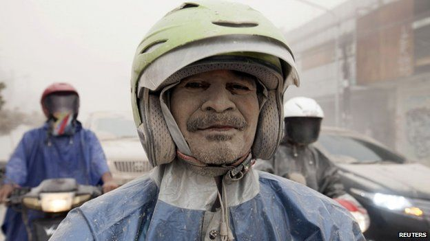 A man covered with ash from Mount Kelud is seen on his motorcycle in Yogyakarta, 14 February 2014