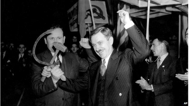 Earl Browder, right, Communist US presidential candidate, crosses a hammer with a sickle held by Charles Krumbein, state secretary of the Communist Party, as they stand before a crowd gathered for the final rally of the campaign at Madison Square Garden in New York City, 2 November 1936