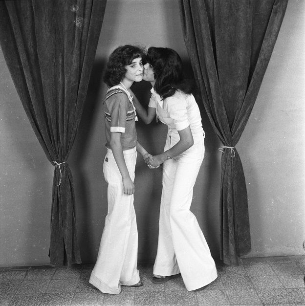 Two girls in flared trousers kiss each other on the cheek