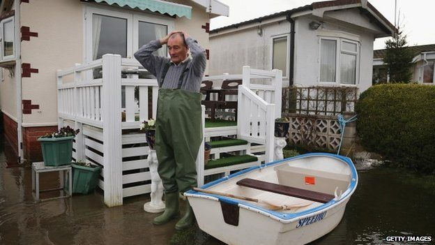 Man surveys flood damage at his Chertsey home, which backs on to the Thames