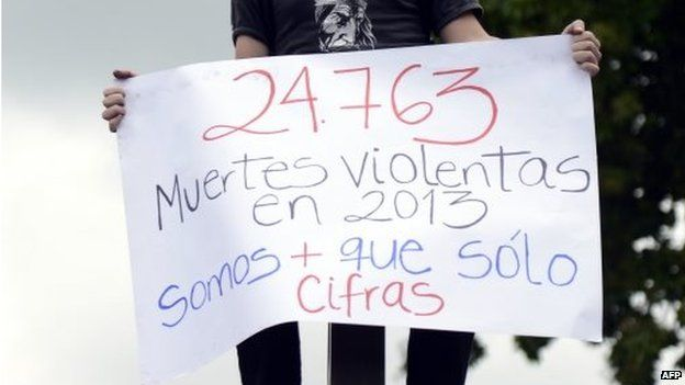 """A man holds a banner reading """"24,763 violent deaths in 2013 - we are more than just figures"""""""