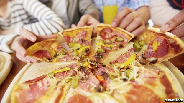 People taking a slice of pizza