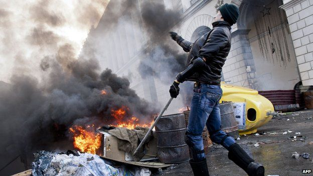 A Ukrainian protester throws a rock during clashes in Kiev