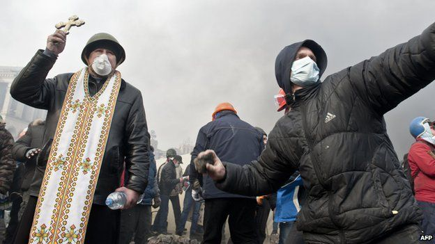 A protester throws rocks while another holds a cross