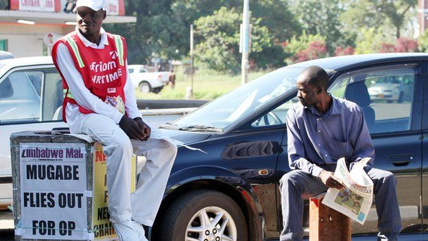 """Men in Harare, Zimbabwe, near a poster with the headline: """"Mugabe flies out for op"""" - February 2014"""