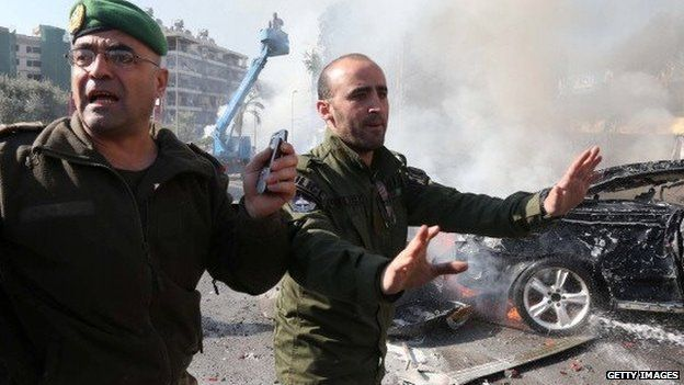 Lebanese security forces stand in front of wreckage of a car blast in Beirut on February 19, 2014.