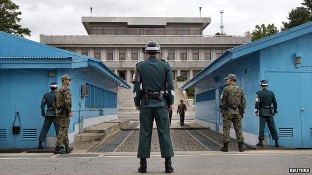 South Korean soldiers look towards the North Korean side as a North Korean solder approaches the UN truce village building that sits on the border of the Demilitarized Zone (DMZ), the military border separating the two Koreas