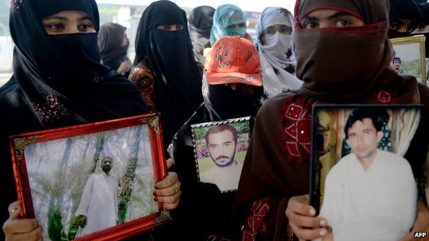 Pakistani Baloch women carry photographs of missing ethnic Balochs at Hub district as they march towards Karachi from Quetta, the capital of Baluchistan Province on 21 November 2013