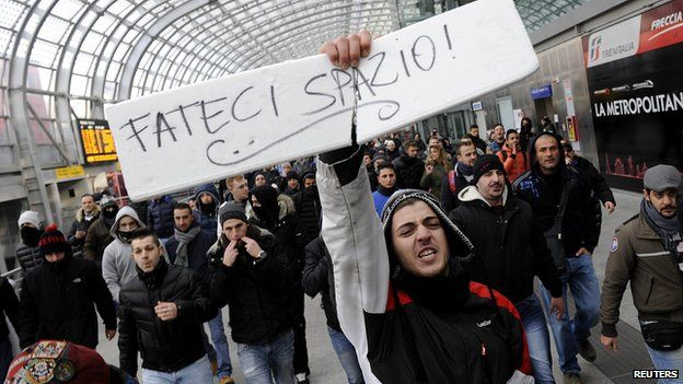 """A protester at Turin train station holds a sign reading """"Make room for us"""" during protests against targets including banks and the tax collection agency, Dec 2013"""