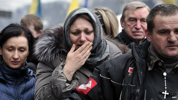 A woman weeps during a funeral service for the anti-government protesters