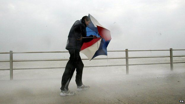 Man with umbrella battling the elements on the seafront