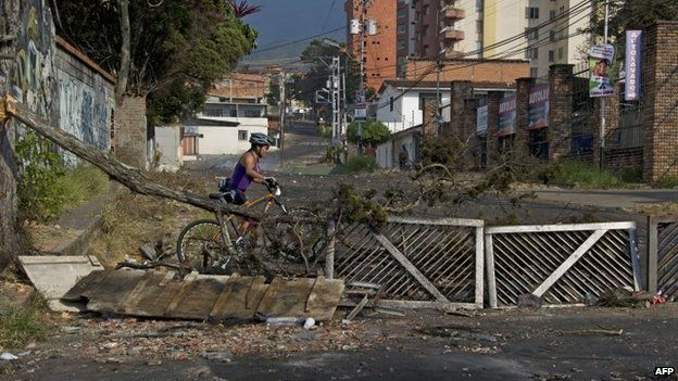 A cyclist goes through a road blocked to protest against the government of Venezuelan President Nicolas Maduro in San Cristobal on 23 February, 2014