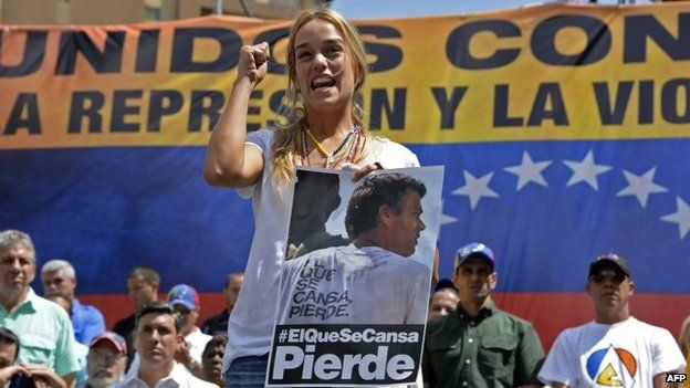 Lilian Tintori, wife of opposition leader Leopoldo Lopez, holds a poster during a protest against the government of Venezuelan President Nicolas Maduro in Caracas on 22 February, 2014