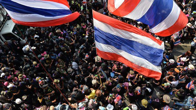 Anti-government protesters wave Thai flags during a rally outside the national police headquarters in Bangkok on 26 February 2014.