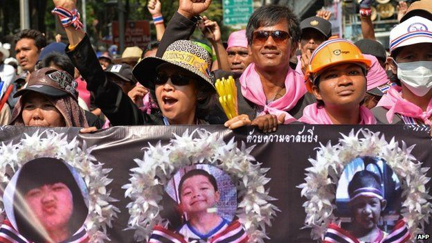 Anti-government protesters hold posters of victims of a recent bomb blast, six-year-old Patcharakorn Yosubon (L) and her brother four-year-old Koravitch Yosubon (C), as they march in a rally outside the national police headquarters in Bangkok, 26 February 2014