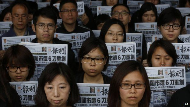 Editorial staff members of the Ming Pao newspaper hold the front page of their newspaper outside the Ming Pao office in Hong Kong, 27 February 2014
