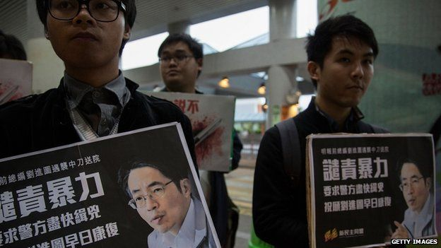 Pro-democracy activists hold a sign with an image of former chief editor of the Ming Pao daily Kevin Lau Chun-to as they attend a candlelight vigil at a hospital, Hong Kong, 26 February 2014