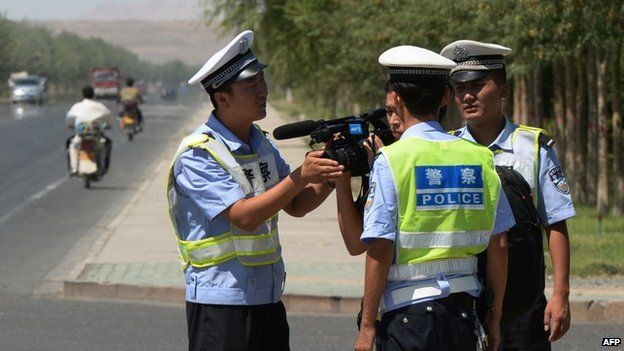 File photo of Chinese police detaining a journalist at a checkpoint on the road to Lukqun town in Xinjiang province, 28 June 2013