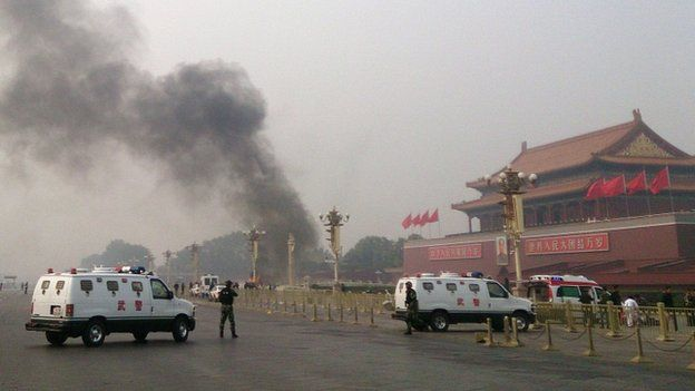 This file photo taken on 28 October 2013 shows police cars blocking off the roads leading into Tiananmen Square as smoke rises into the air after a vehicle loaded with petrol crashed in front of Tiananmen Gate in Beijing