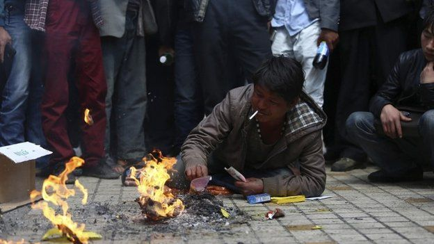 Man, whose relative was killed in a knife attack, lies on the floor as he burns offerings at Kunming railway station in Kunming