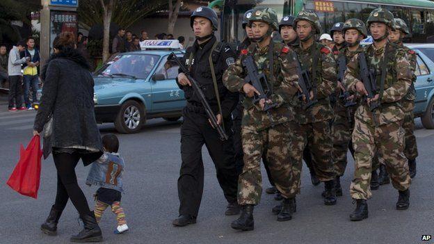 Armed policemen patrol a street near Kunming Railway Station (3 March 2014)