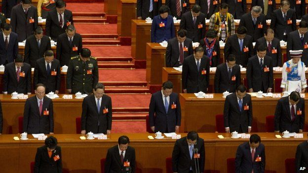 China's top leaders including Chinese President Xi Jinping, centre, bow their heads to observe a minute of silence during the opening session of the annual National People's Congress in Beijing's Great Hall of the People, China, 5 March 2014