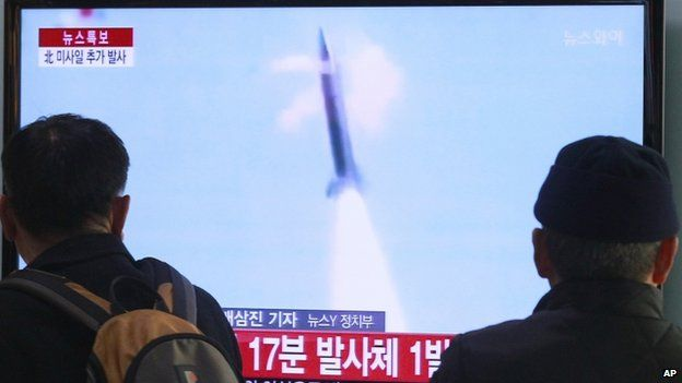 People watch TV reporting North Korea's missile test at Seoul Railway Station in Seoul, South Korea, 4 March 2014