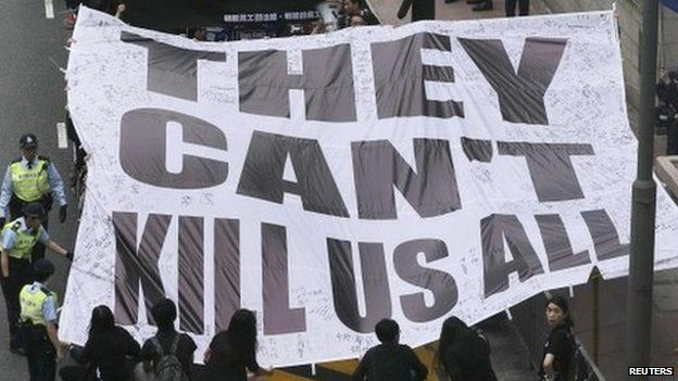 """Demonstrators carry a banner that reads """"They can't kill us all"""" during a march against violence on journalists in Hong Kong, 2 March 2014"""