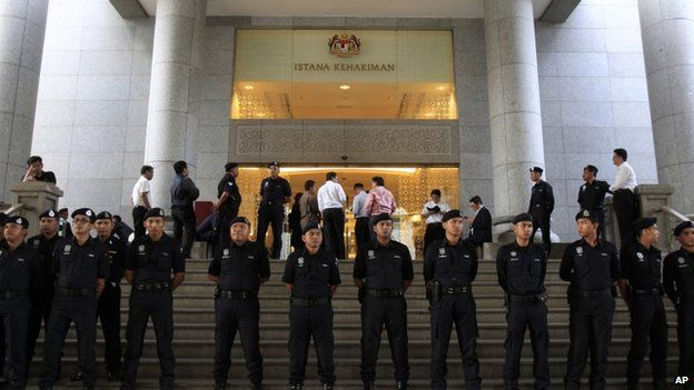 Malaysian police officers stand guard outside a courthouse in Putrajaya, Malaysia, Friday, March 7, 2014