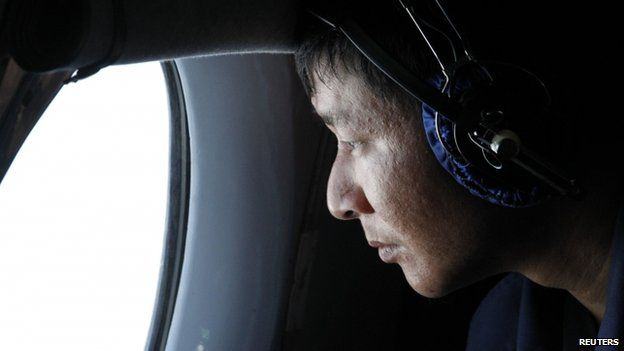 A military officer looks out of a window during a search and rescue mission onboard an aircraft belonging to the Vietnamese air force off Vietnam's Tho Chu island, 10 March 2014