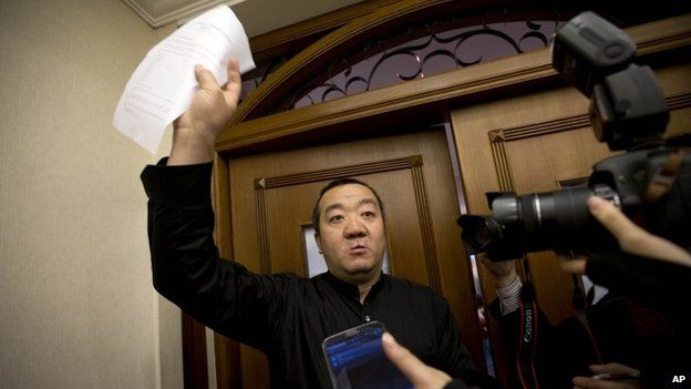 A Chinese relative of passengers aboard a missing Malaysia Airlines plane speaks to the media outside a holding room at a hotel in Beijing