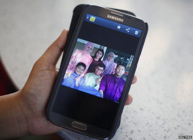 Arni Marlina, 36, a family member of a passenger onboard Flight MH370, shows a family picture on her mobile phone, at a hotel in Putrajaya, Malaysia, 9 March