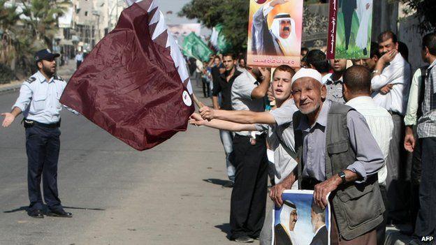 People wave Qatar's flag during a visit to Gaza by the then Emir, Sheikh Hamad bin Khalifa Al Thani