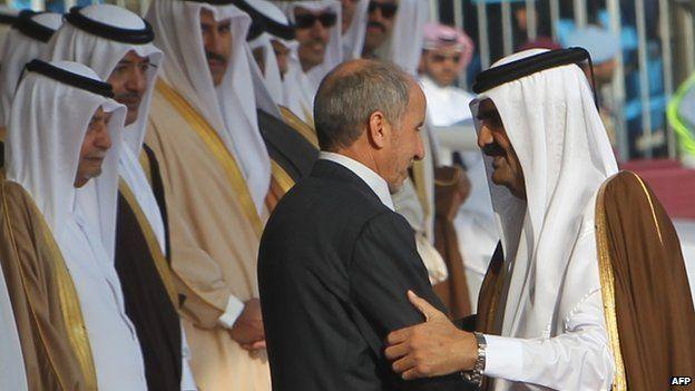 Qatar's Emir Sheikh Hamad bin Khalifa Al Thani embraces the former head of Libya's National Transitional Council, Mustafa Mohammed Abdul Jalil in December 2011