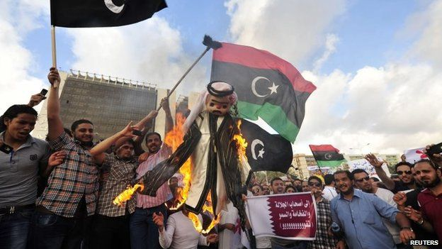 Protesters burn an effigy of Qatar's emir as they wave the flags of Cyrenaica and Libya during a rally against the Muslim Brotherhood and Qatar in Benghazi (10 May 2013)
