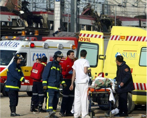 Rescue workers evacuate an injured person following the bombing at Atocha railway station in Madrid