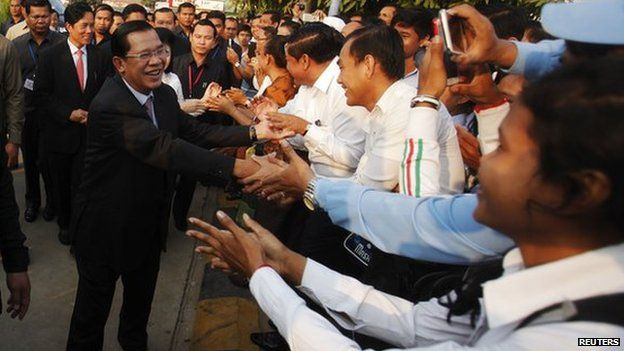 """Hun Sen greets his supporters as he arrives for a ceremony at Koh Pich island to mark the 35th anniversary of the toppling of Pol Pot""""s Khmer Rouge regime in Phnom Penh"""